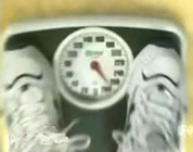 funny diet videos link; thumb of feet in athletic shoes on a scale