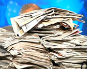 funny video about the death of newspapers link; thumb of man behind large stack of newspapers